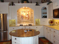 white kitchen with tusccan backsplash and round island