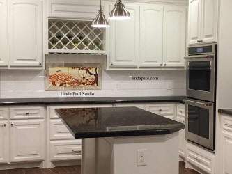 black and white kitchen with wine tile mural above stove