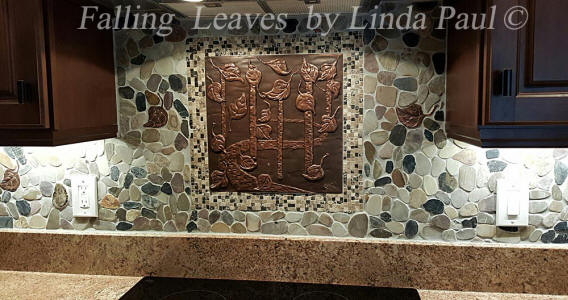 art and crafts style backsplash with leaves and pebbles